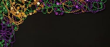 Purpurfärgade, guld- och gröna Mardi Gras pärlor royaltyfria bilder