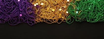 Purpurfärgade, guld- och gröna Mardi Gras pärlor arkivfoto