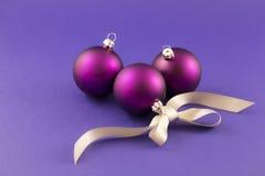 Purpurfärgade julbollar med det gråa bandet Royaltyfria Foton