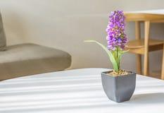 Purpurfärgade konstgjorda blommor i liten kruka Arkivfoto