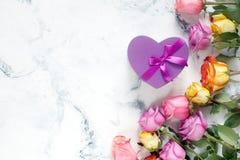 Purpurfärgade och gula rosor, ask som är närvarande på vit bakgrund Royaltyfri Fotografi