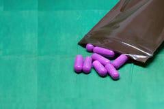 Purpurfärgade preventivpillerar som kapslar plaskar ut från medicin, innehåller påsen arkivbilder