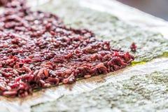 Purpurfärgade ris på ett ark av havsväxt som är klart för ett strikt vegetariansushimål arkivfoto