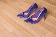 Purpurfärgade sammetskohäl på träbakgrund kopiera avstånd Härlig modeelegans och lyxiga skor för hög häl arkivbild