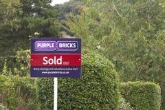 Purpurfärgade tegelstenar - UK-online-fastighetsmäklaretecken Fotografering för Bildbyråer