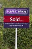 Purpurfärgade tegelstenar - UK-online-fastighetsmäklaretecken Arkivbild