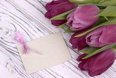 Purpurfärgade tulpan med vitbok på en vit träbakgrund med kortet för text Kvinnas dag 8 mars dagmamma s Royaltyfria Foton