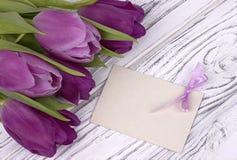 Purpurfärgade tulpan med vitbok på en vit träbakgrund med kortet för text Kvinnas dag 8 mars dagmamma s Fotografering för Bildbyråer