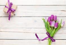Purpurfärgade tulpan och gåvaask över trätabellen Arkivfoton