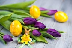 Purpurfärgade tulpan och gula påskägg med kaninstatyetten på träbakgrund Royaltyfri Bild