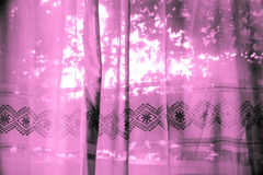 Purpurfärgade tyggardiner med ljus Royaltyfri Bild