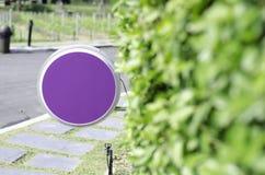 Purpurfärgat cirkeltecken och träbågar i trädgården arkivfoto