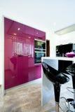 Purpurfärgat möblemang i ett modernt kök Arkivbilder