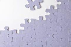 Purpurfärgat oavslutat pussel på en vit tabell royaltyfri bild
