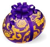 Purpurfärgat och guld- påskägg med pilbågen Royaltyfria Foton