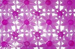 Purpurfärgat rubber mattt för bad med blommamodellen som bakgrund Arkivbild