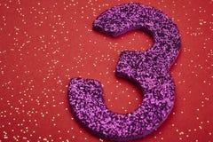Purpurfarbe der Nr. drei über einem roten Hintergrund jahrestag Lizenzfreie Stockfotos