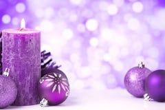Purpurfärgad julplats med struntsaker och stearinljus Arkivbild