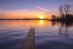 Purpurfärgad solnedgång över ganska sjön Arkivbild