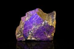 Purpurite mineralisk sten framme av svart fotografering för bildbyråer