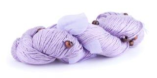 Purpurowa przędza z drewnianymi piłkami i tkaniną opuszcza odosobniony na białym tle Fotografia Stock