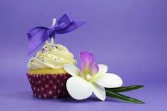 Purpurowa temat babeczka z storczykowym kwiatem Zdjęcia Stock