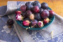 Purpurowe śliwki w zielenieją talerza Zdjęcia Stock