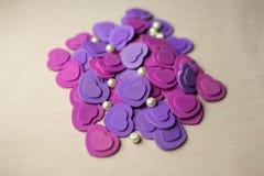 Purpurowe Serca i perły kłama na beżowej tkaninie Obrazy Royalty Free