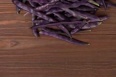 Purpurowe smyczkowe fasole na drewnianym tle Fotografia Royalty Free