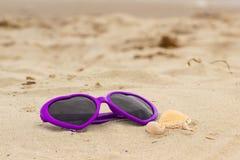 Purpurowi okulary przeciwsłoneczni kształtowali serce z skorupami na piasku przy plażą Zdjęcia Stock
