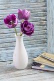 Purpurowi tulipany w białej ceramicznej wazie i stercie książki na błękitnym nieociosanym drewnianym tle Zdjęcie Stock