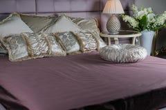 Purpurowy łóżko z beżowymi poduszkami i klasycznym round stołem Zdjęcia Royalty Free