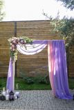 Purpurowy ślubu łuk dekorujący z kwiatami, bzem i menchia materiałem, Piękna platforma dla ślubnej ceremonii pod otwartym Obraz Stock