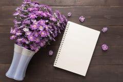 Purpurowy krajacza kwiat waza i notatnik jesteśmy na drewnianym Zdjęcia Royalty Free