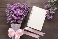 Purpurowy krajacza kwiat waza z faborkiem i notatnik jesteśmy dalej Zdjęcia Stock