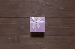 Purpurowy prezenta pudełko jest na drewnianym tle z pustą przestrzenią Obrazy Stock
