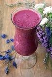 Purpurowy smoothie z błękitnym i białym kwiatem zdjęcie stock