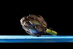 Purpurrote Artischocke an der Hintergrundbeleuchtung in einer Dunkelheit umgebend lizenzfreies stockbild