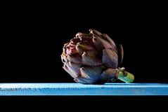 Purpurrote Artischocke an der Hintergrundbeleuchtung in einer Dunkelheit umgebend stockfotografie