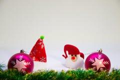 Purpurrote Bälle, Santa Claus in einem roten Hut und im Zubehör für Weihnachten Stockfotografie