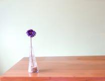 Purpurrote Blume im Glasvase setzte an Holztisch Stockbild