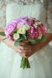 Purpurrote Blumen in den Händen der Braut Lizenzfreie Stockfotos