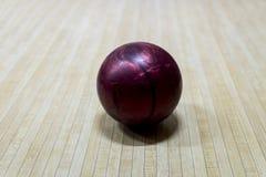 Purpurrote Bowlingkugel auf der Bahn in der rollenden Mitte stockfotos