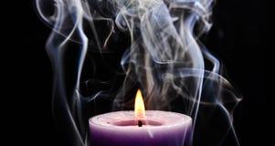 Purpurrote brennende Kerze stockfotos