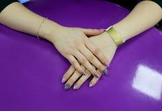 Purpurrote gl?nzende Manik?re auf violettem Hintergrund stockfoto