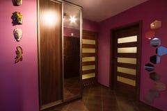 Purpurrote Halle mit Garderobe Stockfotografie