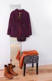 Purpurrote Jacke, die an einem Spiegel hängt Stockfotos
