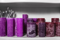 Purpurrote Kerzen auf einem Regal Wenig Tabelle verziert mit Kerzenlicht, Vase und Büchern Stockfotografie