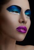 Purpurrote Lippen, blaue Schatten auf den Augen, schwarze Augenbrauen Frauen-Make-upschönheit Stockfoto
