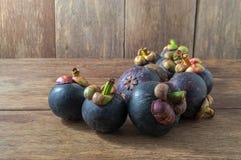 Purpurrote Mangostanfrüchte auf hölzernem Hintergrund Lizenzfreies Stockfoto